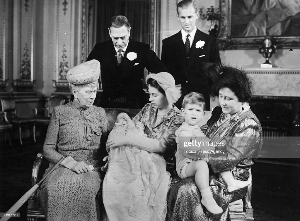 Princess Elizabeth holding Princess Anne with Queen Mary (left) whilst Queen Elizabeth (1900 - 2002) holds Prince Charles (right). King George VI and Prince Philip, Duke of Edinburgh stand behind them after Princess Anne's christening.