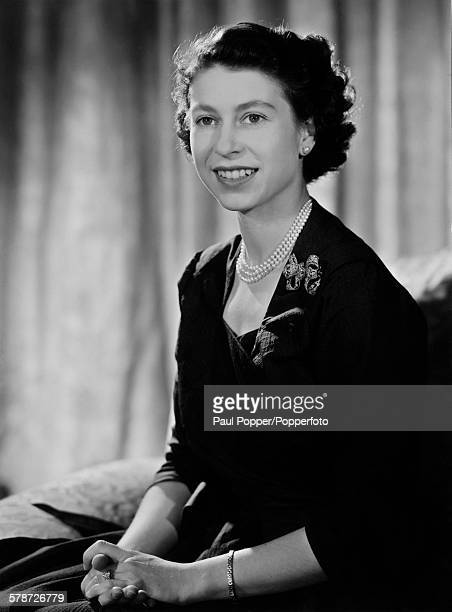 Princess Elizabeth in the drawing room at Clarence House London January 1952 She is wearing an afternoon dress of slateblue figured silk