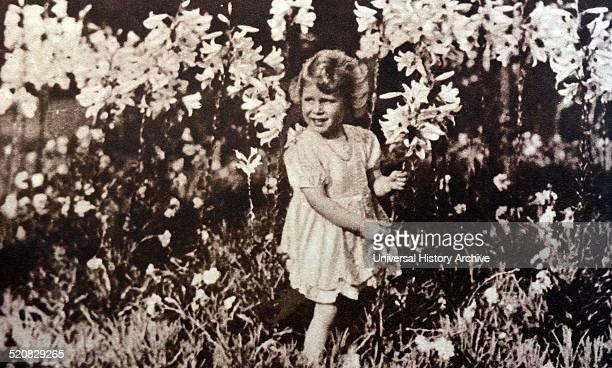Princess Elizabeth later Queen Elizabeth II as a child gathering flowers in a garden 1930