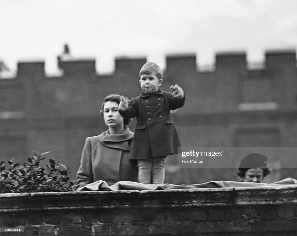 Princess Elizabeth (later Queen Elizabeth II), left, and <a gi-track='captionPersonalityLinkClicked' href=/galleries/search?phrase=Prince+Charles&family=editorial&specificpeople=160180 ng-click='$event.stopPropagation()'>Prince Charles</a> watching a procession, during the visit of Queen Juliana of the Netherlands, from the wall of Clarence House, London, 22nd November 1950.