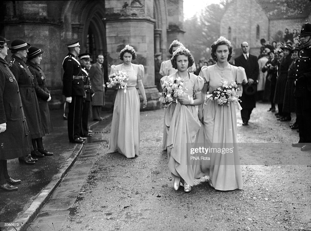 Princess Elizabeth, Princess Alexandra of Kent and Princess Margaret (1930 - 2002) leave Romsey Abbey, Hampshire in their bridesmaids' dresses after attending the wedding of Captain Lord Brabourne and Patricia Mountbatten.