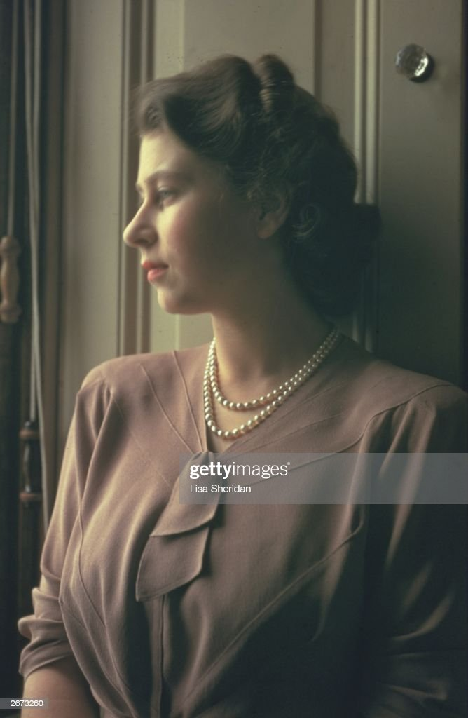 Princess Elizabeth standing by a window in the State Apartments at Buckingham Palace.