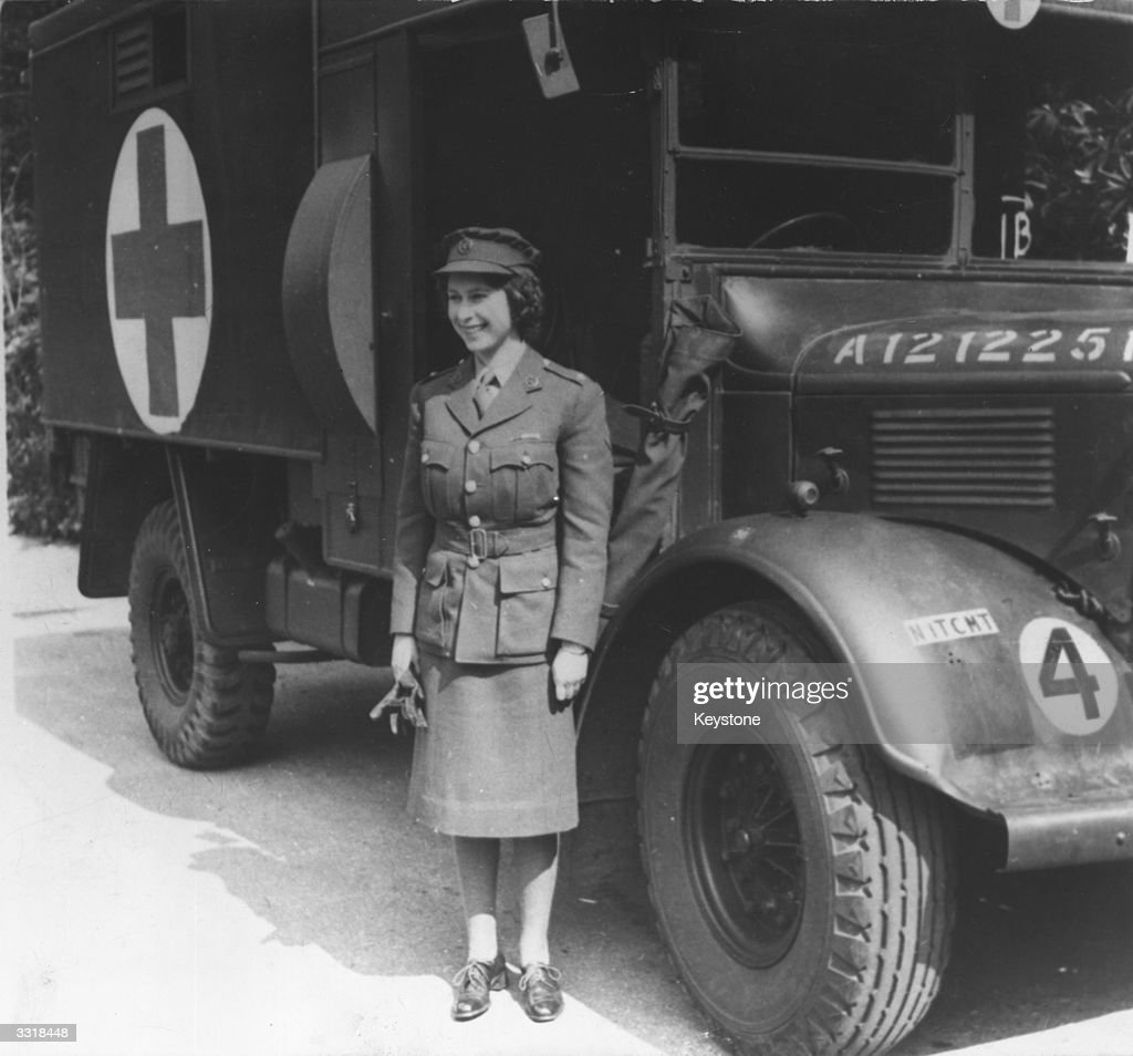 Princess Elizabeth, standing by an Auxiliary Territorial Service first aid truck wearing an officer's uniform.