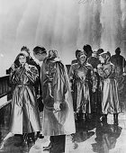 Princess Elizabeth stands dressed in waterproof raincoat with Mayor of Niagara Falls Ernest Hawkins as they view Niagara Falls at Table Rock Ontario...