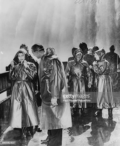 Princess Elizabeth stands dressed in waterproof raincoat with Mayor of Niagara Falls Ernest Hawkins as they view Niagara Falls at Table Rock Ontario...