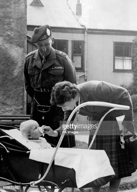 Princess Elizabeth stoops to wipe baby Princess Anne's nose before introducing her to Lieutenant Colonel Nielson who commanded the 1st Argylls in...