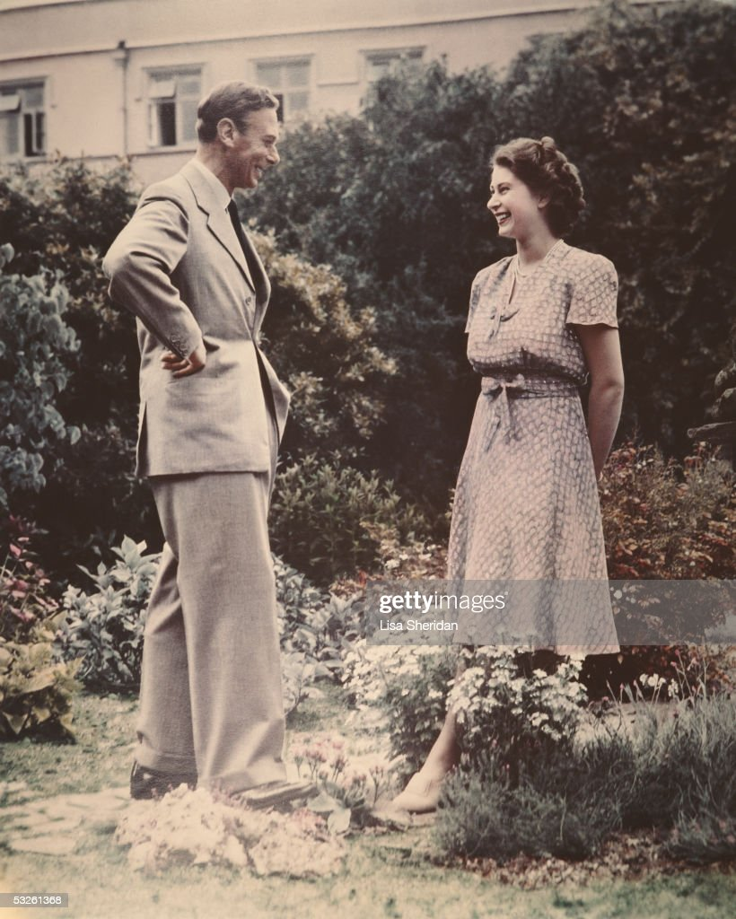 Princess Elizabeth, the future Queen Elizabeth II conversing with her father, King George VI (1895 - 1952) in a garden, 8th July 1946.