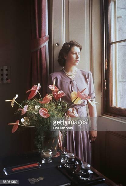 Princess Elizabeth the future Queen Elizabeth II gazes through a window near an exotic floral arrangement 1946