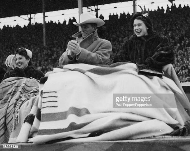 Princess Elizabeth wears a Canadian mink coat and Prince Philip wears a 'ten gallon hat' covered by blankets as they watch a rodeo with the Mayoress...