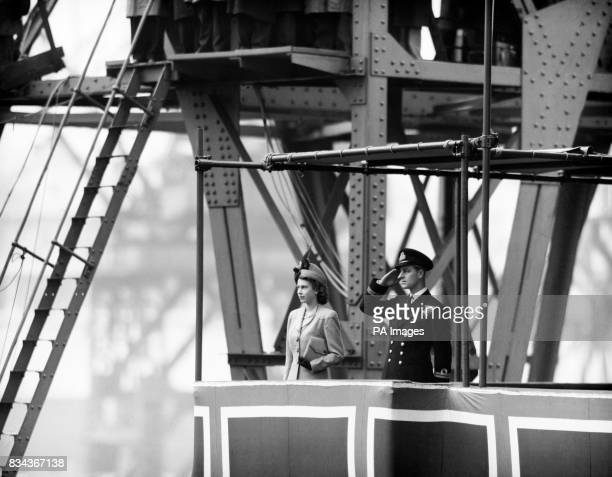 Princess Elizabeth with Lieutenant Philip Mountbatten saluting beside her watches the Caronia slide down into the water during her launching at John...