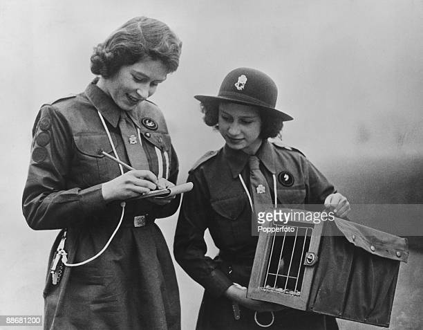 Princess Elizabeth writes a message to Chief Guide Lady Olave BadenPowell as her younger sister Princess Margaret Rose looks on 20th February 1943...