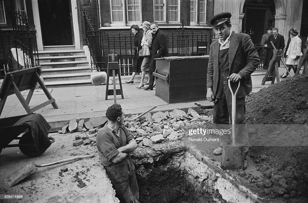 Princess Grace of Monaco and Prince Rainier III walking past workmen digging on the street 4th December 1959