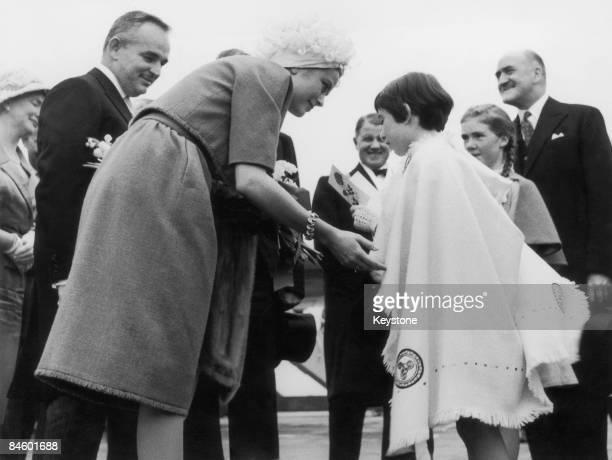 Princess Grace of Monaco receives a bouquet from the granddaughter of Irish statesman Eamon de Valera on her arrival in Dublin for the Festival of...