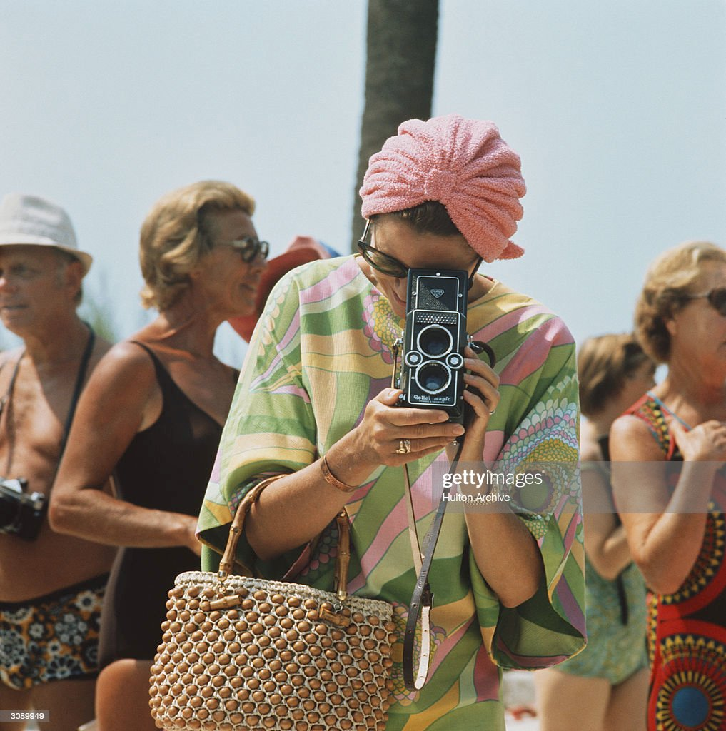 Princess Grace of Monaco taking a photograph at a swimming competition at Palm Beach Monte Carlo