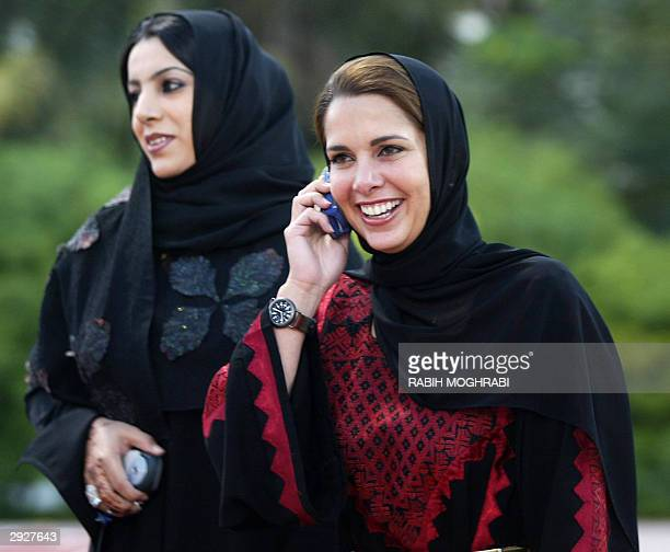Princess Haya of Jordan talks on the phone as she takes a stroll with Emirati women during a training session of female players of the All Women Arab...