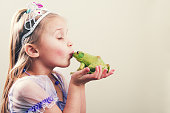 a little girl princess kissing a frog with copy space.
