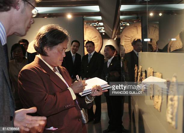 Princess Maha Chakri Sirindhorn from Thailand daughter of Thai King Bhumibol Adulayadej takes notes as she visits in Paris on March 19 the exhibition...