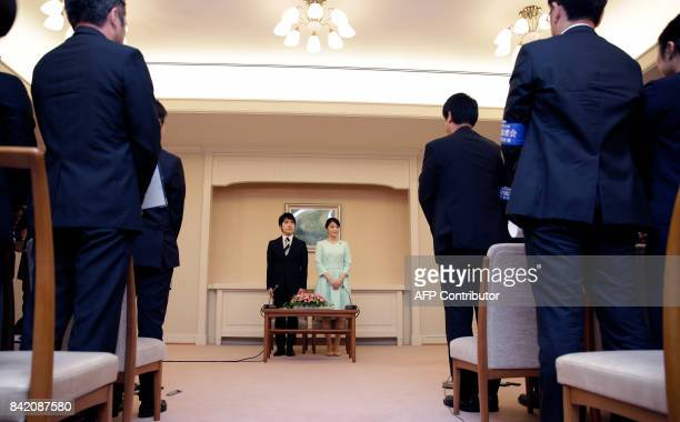 Princess Mako the eldest daughter of Prince Akishino and Princess Kiko and her fiancee Kei Komuro stand in front of the media during a press...