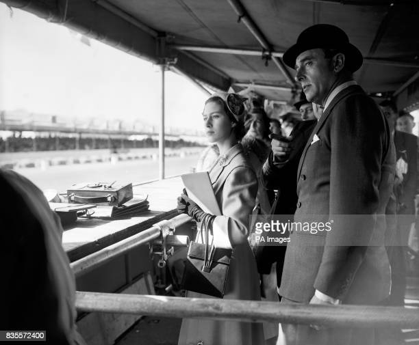 Princess Margaret and Earl Mountbatten watching the race from the pits as cars come in to refuel
