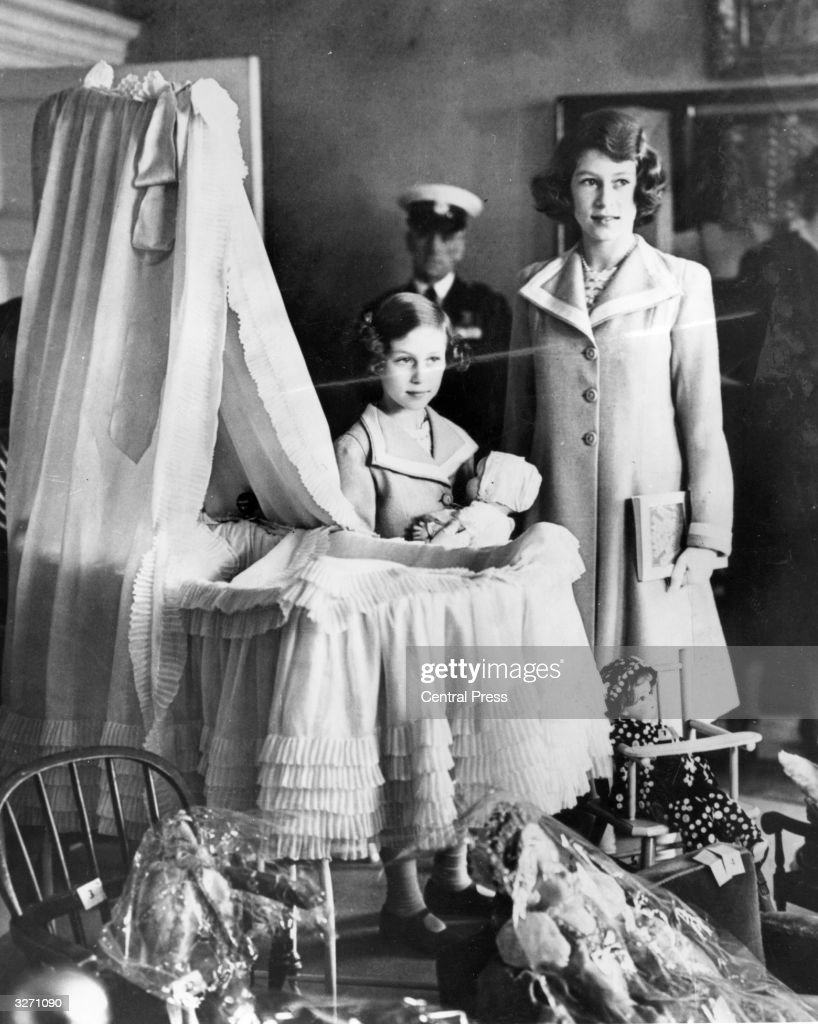 Princess Margaret (1930 - 2002) and Princess Elizabeth (right), admiring their old cot at an exhibition of Royal treasures, at 145 Piccadilly, London, England, their old home before the Duke of York ascended to the throne. The Royal cot later nursed Princess Elizabeth's children.
