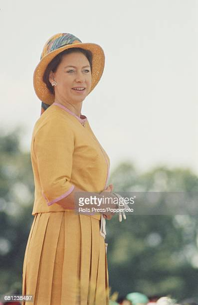 Princess Margaret Countess of Snowdon pictured wearing a matching yellow jacket pleated skirt and straw hat as she attends a parade at the British...