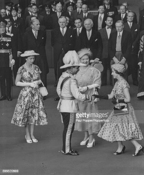 Princess Margaret curseying as she shakes hands with King Faisel II of Iraq with Queen Elizabeth II and Queen Elizabeth the Queen Mother looking on...