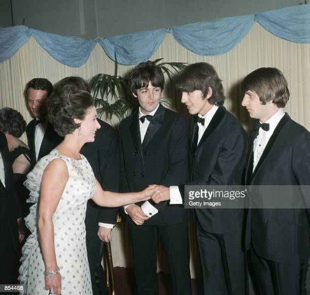 Princess Margaret shakes hands with George Harrison Paul McCartney and Ringo Starr of the British pop group the Beatles in 1965 in London England 58...