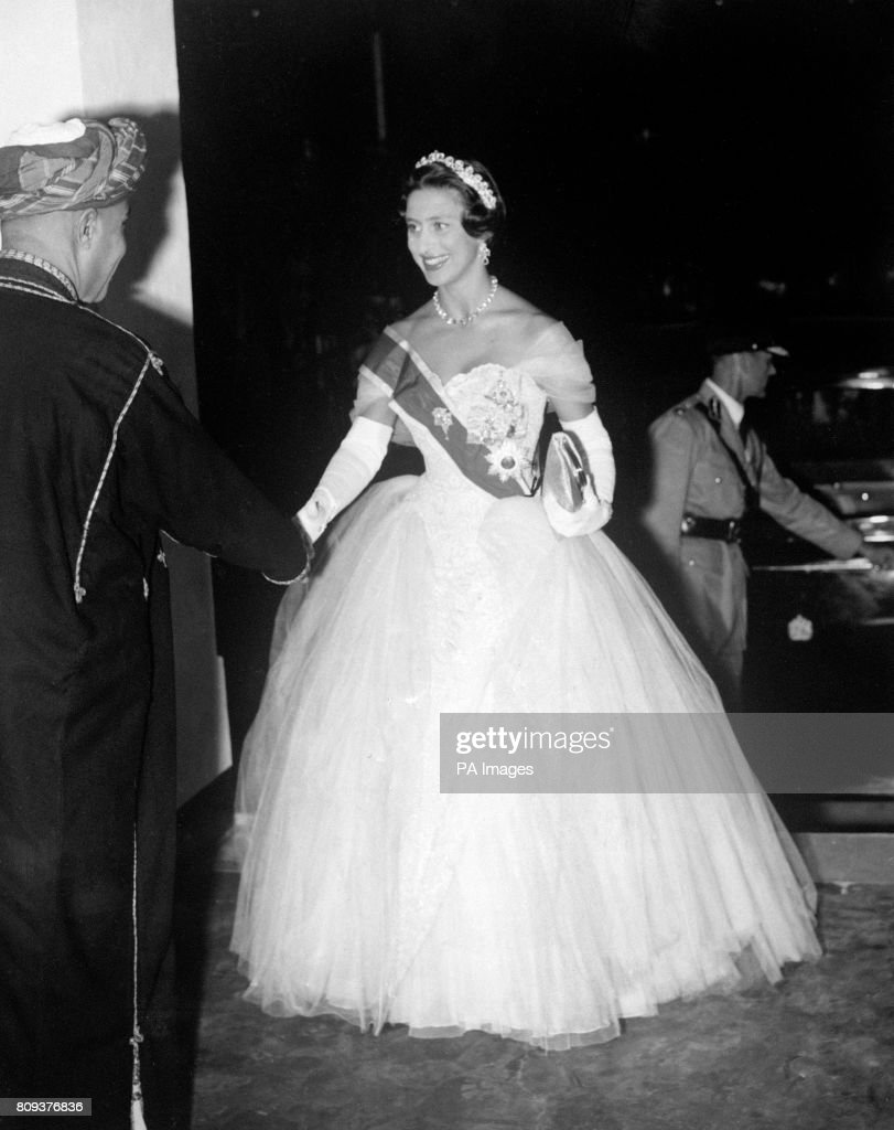 Princess Margaret, wearing a crinoline evening gown slashed with the Ribbon of the Garter and the Cartier Halo Tiara, arrives at the Sultan of Zanzibar's Royal Palace during her East African Tour.