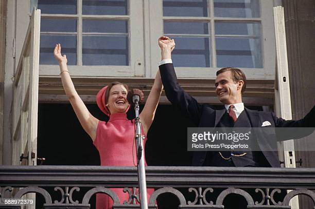 Princess Margrethe of Denmark pictured with her fiance Count Henri de Monpezat as they wave to crowds from a balcony at Amalienborg Palace in...