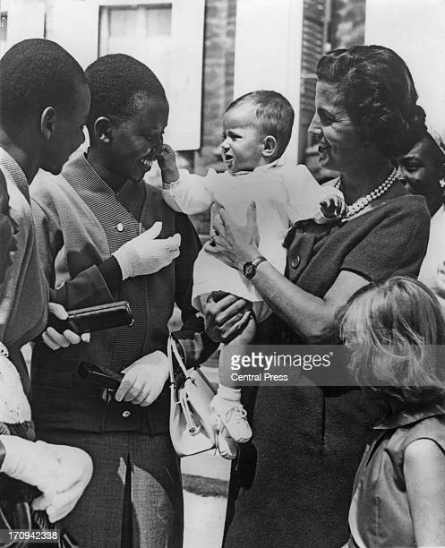 Princess MarieEsmeralda of Belgium held by her mother Princess Lilian of Belgium reaches out to one of the visitors from the Belgian Congo to Laeken...