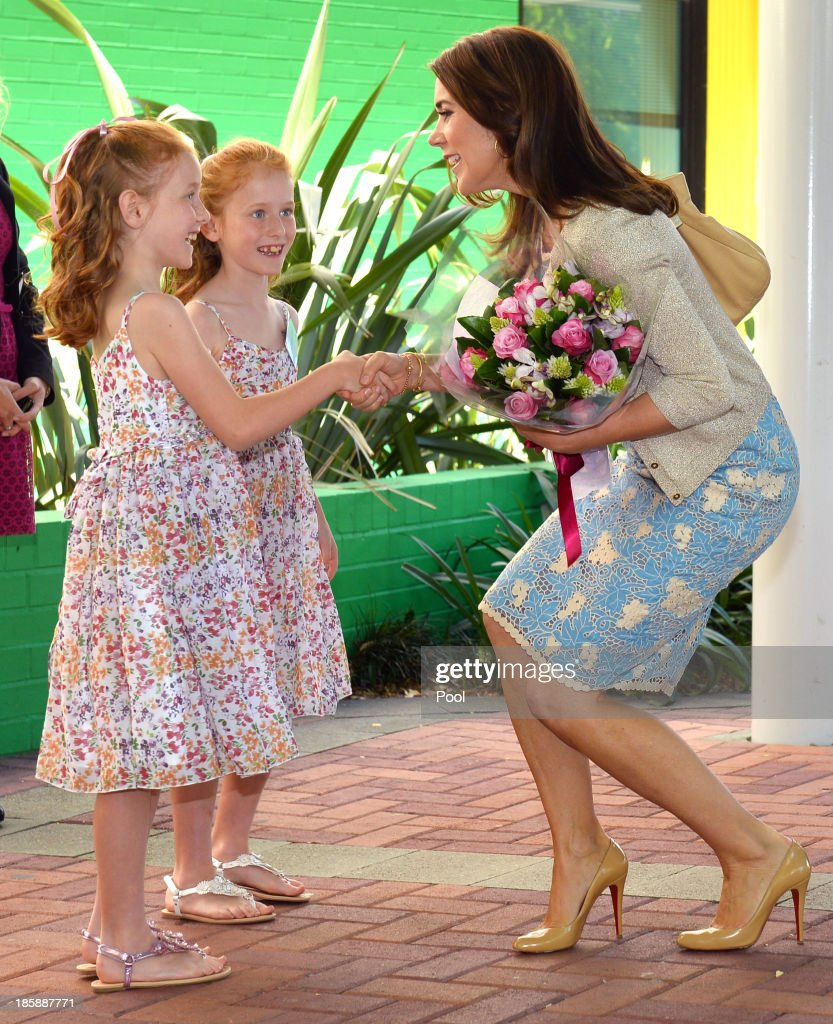Princess Mary of Denmark receives flowers from identical twins Lillian (L) and Charlotte Harding (2nd L) as the royal couple arrive for a visit to the Australian Twin Registry (ATR) at the Sydney Children's Hospital on October 26, 2013 in Sydney, Australia. Prince Frederik and Princess Mary will visit Sydney for five days and will attend events to celebrate the 40th anniversary of the Sydney Opera House and the Danish architect who designed the landmark, Jorn Utzen.