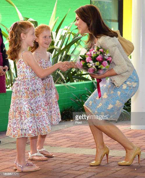 Princess Mary of Denmark receives flowers from identical twins Lillian and Charlotte Harding as the royal couple arrive for a visit to the Australian...