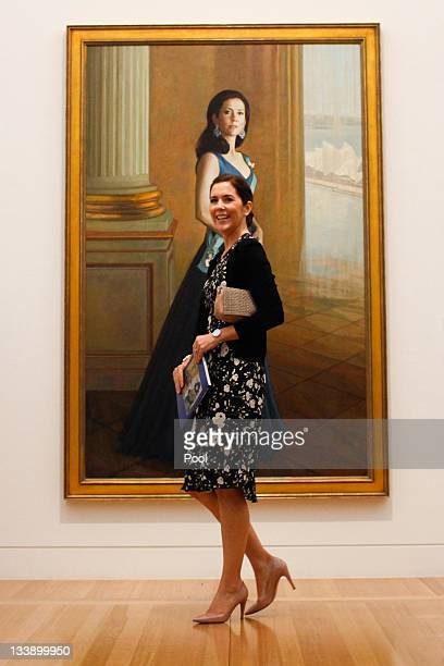 Princess Mary of Denmark stands in front of a painting of herself painted by artist Jiawei Shen at the Portrait Gallery in Canberra on November 22...