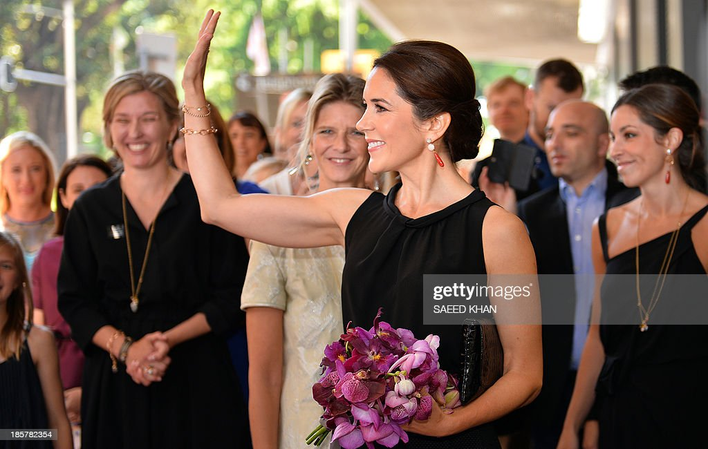 Princess Mary of Denmark (C) waves following the official opening of the official opening of Danish jewellry brand Ole Lynggaard's flagship store in the central business district of Sydney on October 25, 2013. The royal couple, attending celebrations for the 40 year anniversary of the Sydney Opera House, are on a five-day official visit to Australia. AFP PHOTO/ Saeed KHAN / POOL