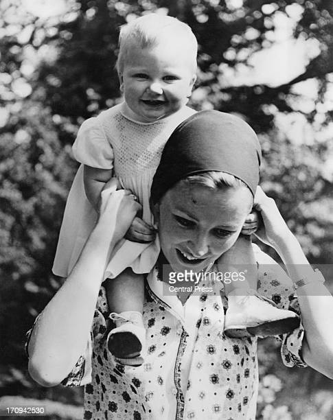 Princess Paola of Belgium holds her daughter Princess Astrid of Belgium on her shoulders on her first birthday Chateau de Belvedere Brussels 5th June...