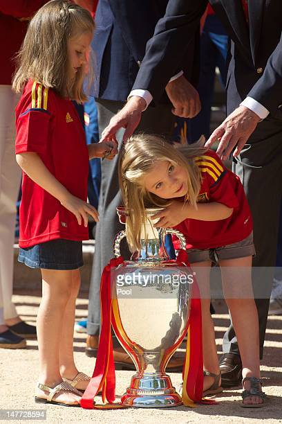 Princess Sofia of Spain reaches into the UEFA EURO 2012 trophy while Princess Leonor of Spain watches as King Juan Carlos I of Spain receives players...
