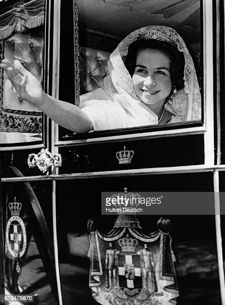 Princess Sophia of Greece waves to wellwishers as she is driven through the streets of Athens after her marriage to King Don Juan Carlos of Spain