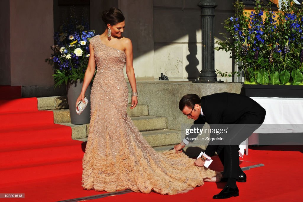 Princess Victoria is helped with her dress by fiance Daniel Westling during the Government Pre-Wedding Dinner for Crown Princess Victoria of Sweden and Daniel Westling at The Eric Ericson Hall on June 18, 2010 in Stockholm, Sweden.