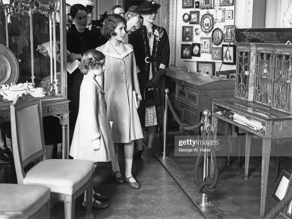 Princesses Elizabeth (later Queen Elizabeth II, centre) and Margaret (1930 - 2002) at an exhibition of royal treasures at 145 Piccadilly, London, 28th July 1939. On the right is Elizabeth's governess Marion Crawford ('Crawfie', 1990 - 1998).