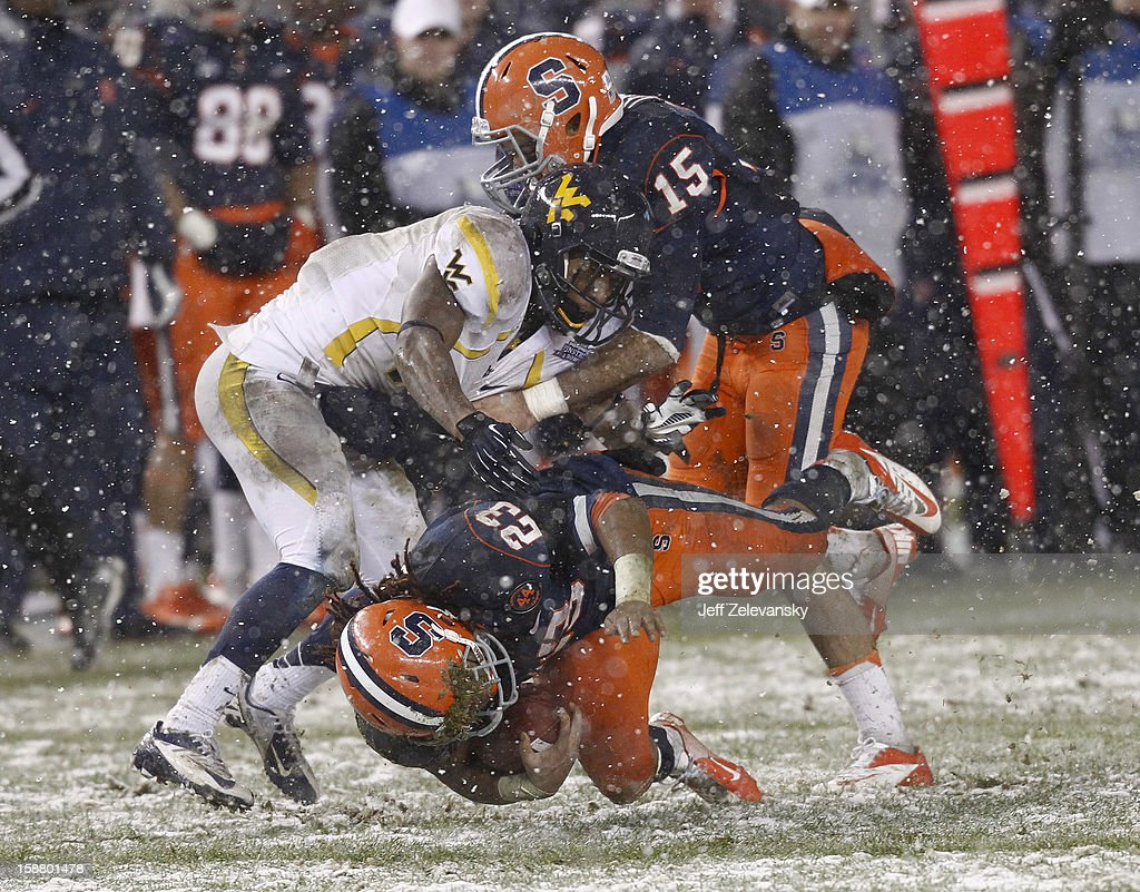 Prince-Tyson Gulley #23 of the Syracuse Orange is tackled by Curtis Smelley #41 of the West Virginia Mountaineers in the New Era Pinstripe Bowl at Yankee Stadium on December 29, 2012 in the Bronx borough of New York City.