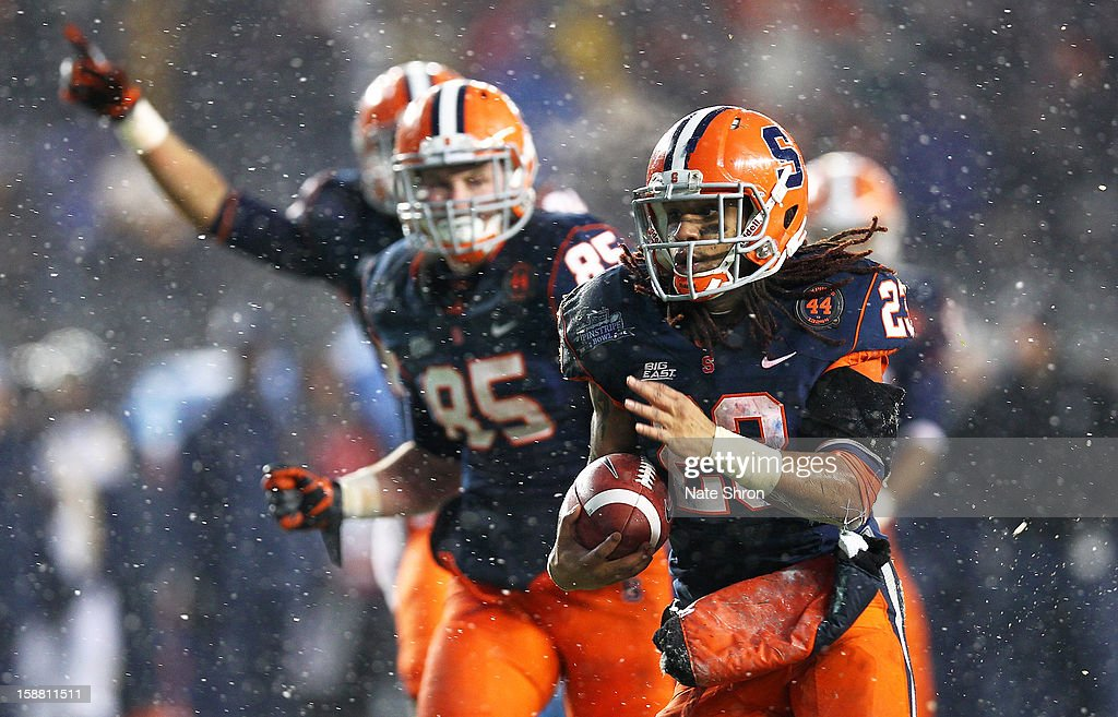 Prince-Tyson Gulley #23 of the Syracuse Orange runs for a touchdown and celebrates with teamate Beckett Wales #85 against the West Virginia Mountaineers during the New Era Pinstripe Bowl at Yankee Stadium on December 29, 2012 in the Bronx borough of New York City.