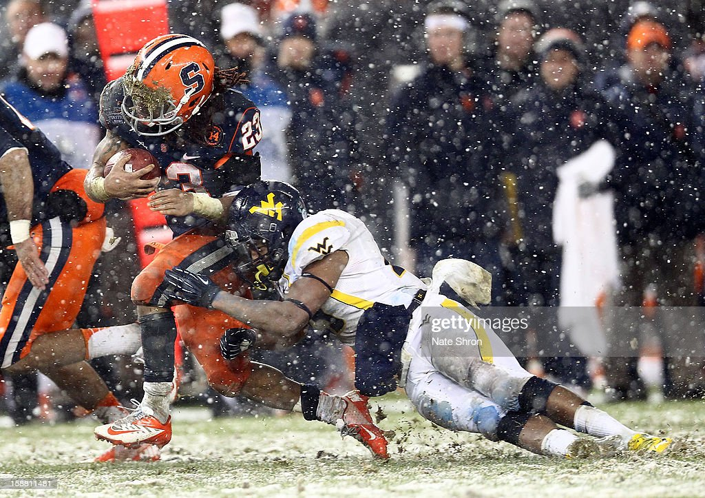 Prince-Tyson Gulley #23 of the Syracuse Orange runs the ball against Darwin Cook #25 of the West Virginia Mountaineers during the New Era Pinstripe Bowl at Yankee Stadium on December 29, 2012 in the Bronx borough of New York City.