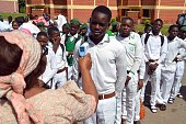 Principal of Tundunwada Secondary School Enenwan Essien checks a student's temperature for Ebola during an assembly in Abuja on September 22 2014...