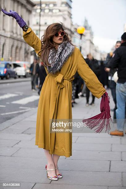 Pringle of Scotland showgoer wears a mustard belted trench coat with a fur shawl a purple glove and red suede fringe purse during The London...