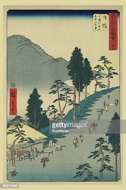Print shows a bird'seye view of pilgrims walking along the Tokaido Road with a small thatchedroof building teahouse or shelter trees and mountain...