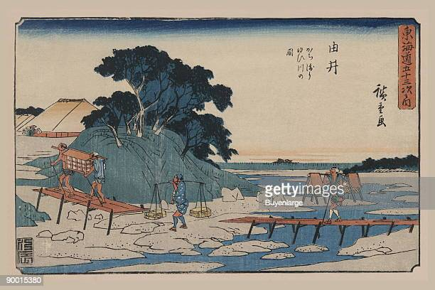 Print shows low wooden walkways spanning a small stream and rough or muddy land areas with two man carrying a palanquin and others with burdens on...