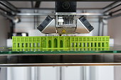 Bright green architectural model being 3D printed on glass printbed