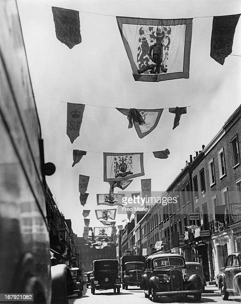 Printed banners of the arms of every monarch since Elizabeth I are displayed in Beauchamp Place Knightsbridge London to celebrate the Coronation 28th...