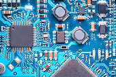 macro top view of a printed circuit board with processors, capacitors and transistors