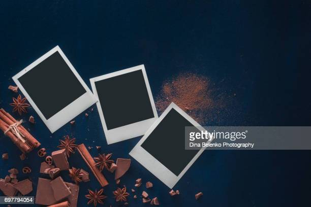 Printed instant photos with cocoa powder, chocolate and cinnamon on a black background